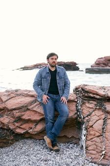 Homme pensif en jeans et veste en jean posant debout sur le rivage appuyé sur des pierres contre le