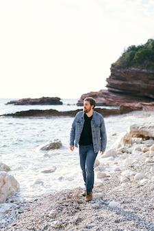 L'homme pensif en jeans et veste en jean se promène le long de la plage de galets en regardant la mer contre le