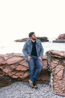 Homme pensif en jeans et veste en jean se tient appuyé contre les pierres près de la mer et regarde