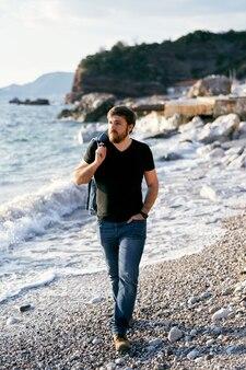 Homme pensif marchant sur une plage de galets avec une veste en jean sur son épaule dans le contexte