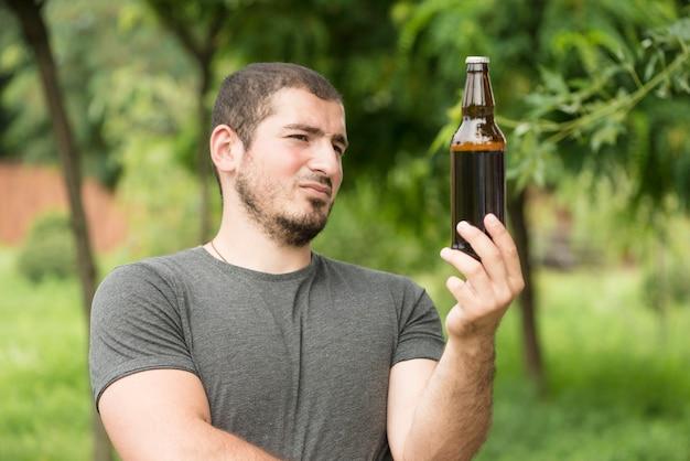 Homme pensif regardant bière