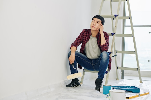 Homme pensif regardant mur peint