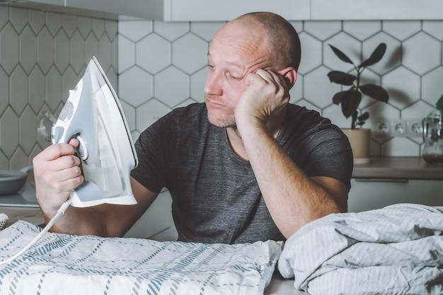 L'homme pensif regarde le fer et le linge de lit