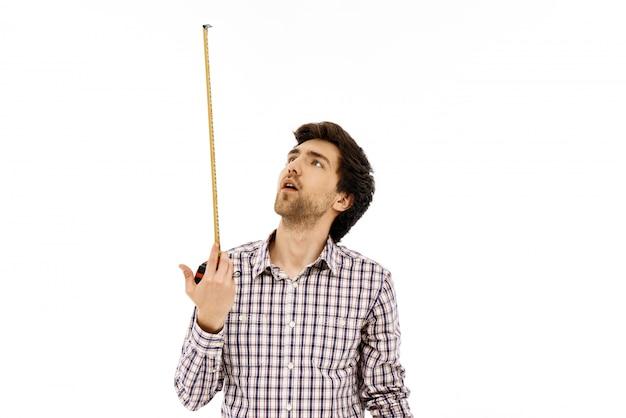 Homme pensif regarder ruban à mesurer