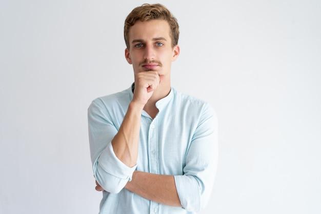 Homme pensif touchant le menton et regardant la caméra