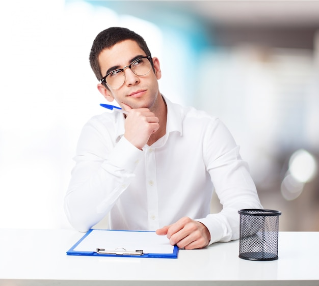 Homme pensive avec une table de stylo à bille point et le contrôle