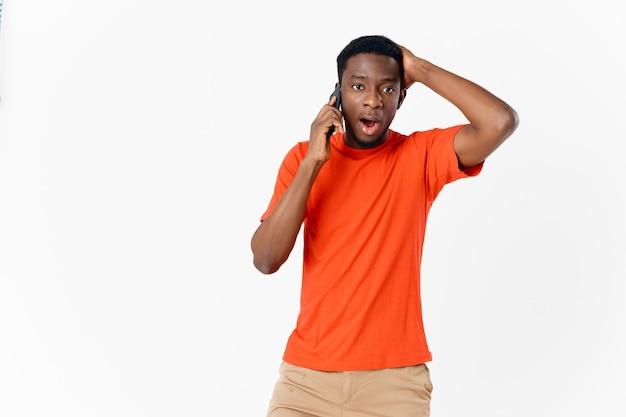 Homme perplexe d'apparence africaine parlant au téléphone sur fond clair