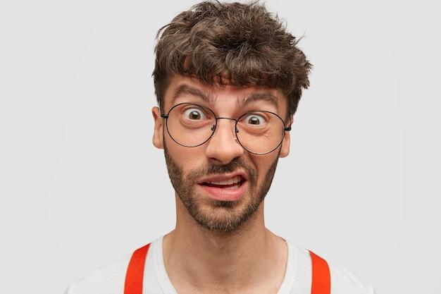 Homme perplexe frustré avec chaume sombre, fronce les sourcils face comme voit quelque chose de désagréable, isolé sur mur blanc