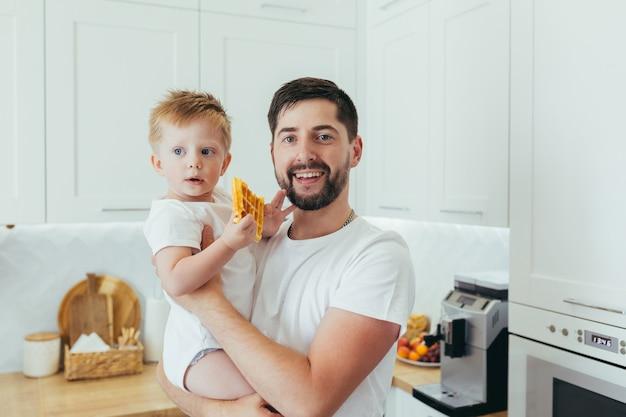 Un homme avec un petit garçon prépare le petit déjeuner, un père et un fils