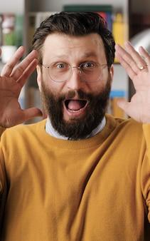 L'homme a peur, est terrifié. un bel homme barbu effrayé à lunettes avec soudainement lève les mains et regarde la caméra, il est très effrayé et juste terrifié. vue rapprochée
