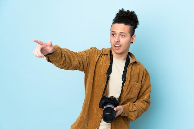 Homme photographe sur bleu isolé pointant vers l'extérieur
