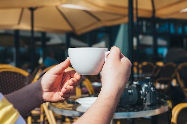 L'homme de photographe boit du café dans un restaurant