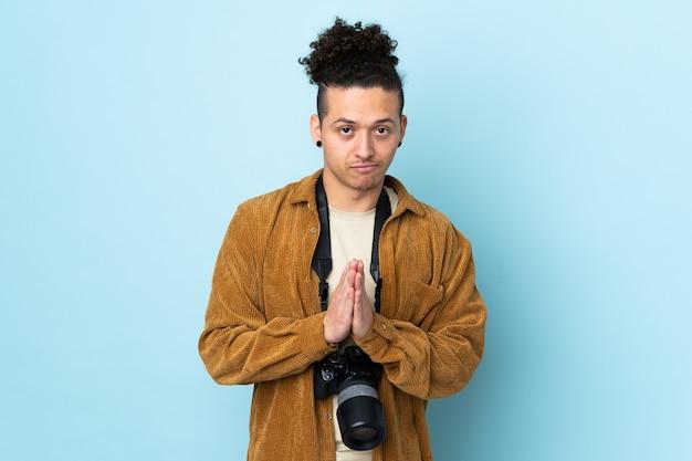 Homme photographe sur fond bleu isolé plaidant