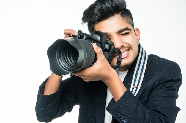 Homme photographe indien tenant son appareil photo sur fond blanc.