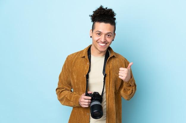 Homme photographe sur mur bleu isolé donnant un geste de pouce en l'air