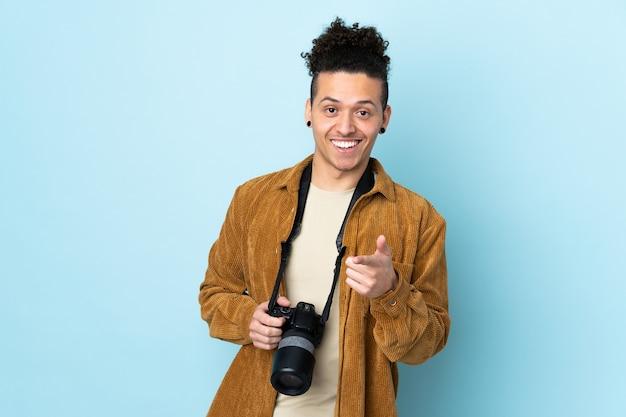 Homme photographe sur mur bleu isolé pointe du doigt sur vous