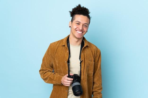 Homme photographe sur mur bleu isolé en riant