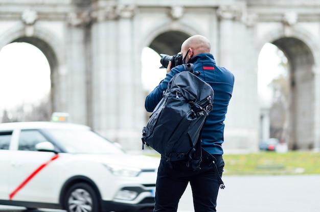 Homme photographe avec sac à dos prenant des photos dans la ville