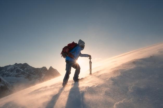 Un homme photographe avec trépied grimpe sur une colline sur le mont ryten dans le blizzard au coucher du soleil