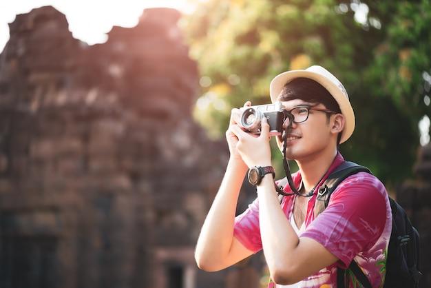 Homme photographe voyageur avec sac à dos prenant une photo avec son appareil photo