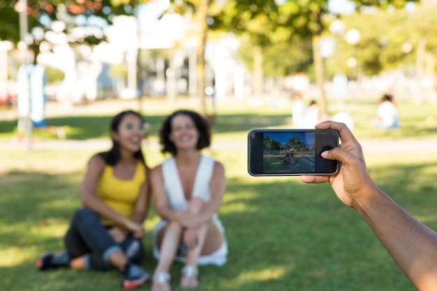 Homme photographiant des amies dans le parc