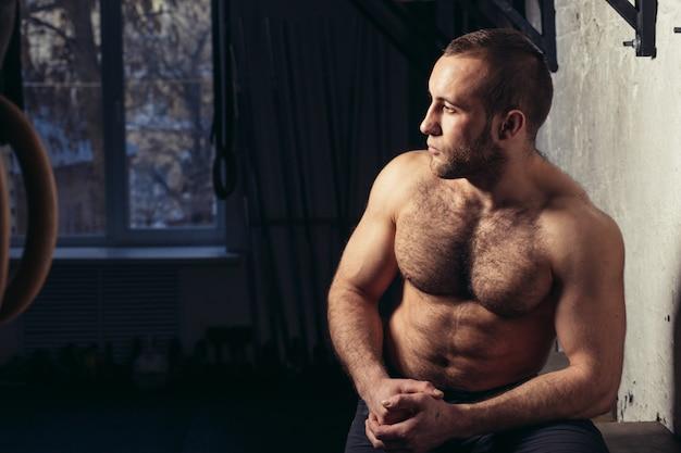 Homme physiquement apte posant dans un club de santé