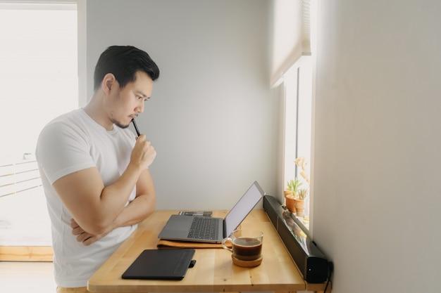 Homme pigiste asiatique réfléchit et travaille sur son ordinateur portable