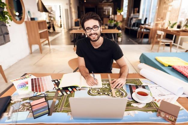 Homme pigiste prenant des notes sur un ordinateur portable assis au bureau.