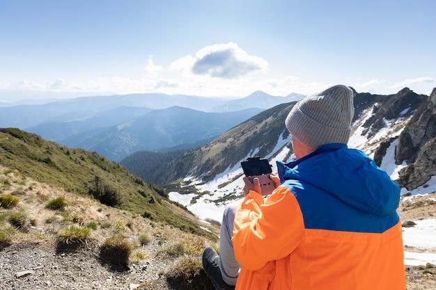 Homme pilotant un drone dans les montagnes. pic de pip ivan. journée ensoleillée et nuageuse en été, crête de marmarosy, carpates, ukraine