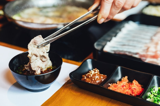 Un homme pince le porc kurobuta bien cuit et le trempe dans une sauce ponzu avec une pince.