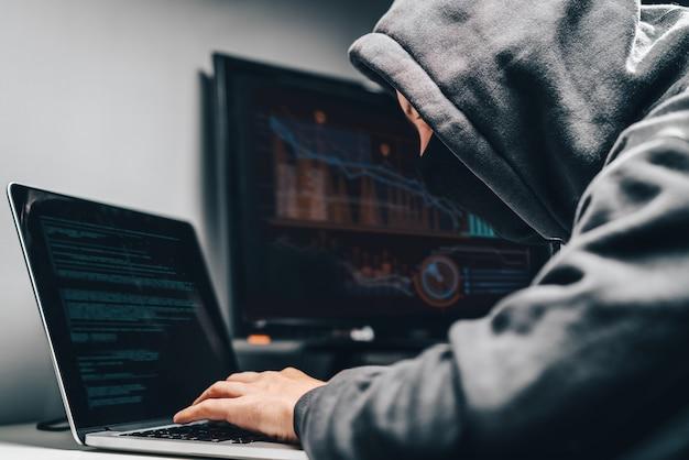 Homme pirate à capuche avec face cachée accédant à des informations personnelles sur un ordinateur dans l'obscurité