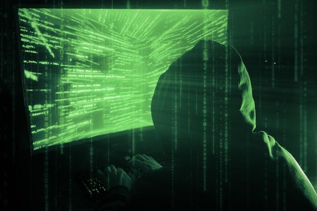 Un homme pirate dans une hotte dans une pièce sombre