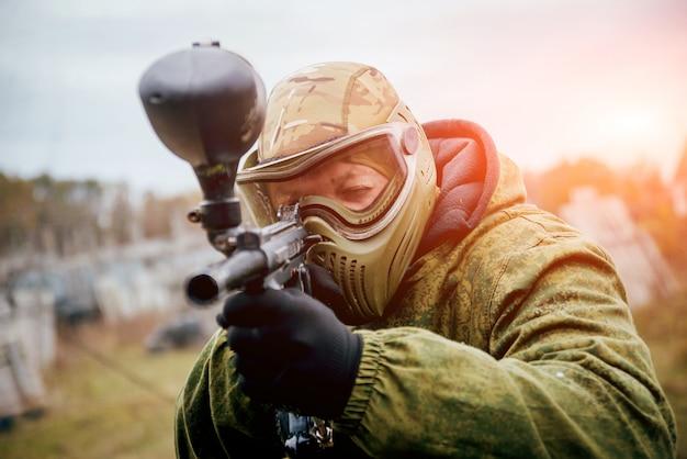 Homme avec pistolet jouant au paintball. en plein air