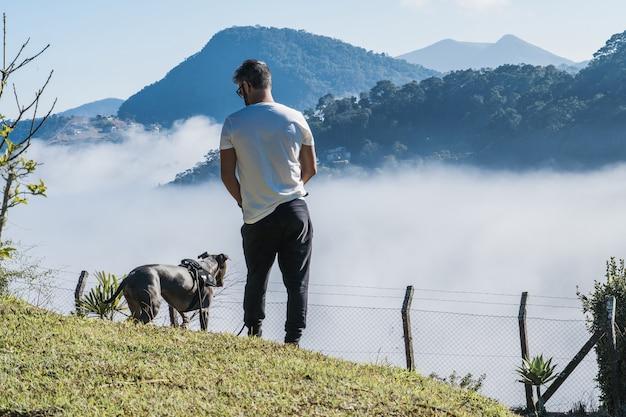Un homme et un pit-bull dog admirant la nature et le grand brouillard dans les montagnes de petropolis brésil