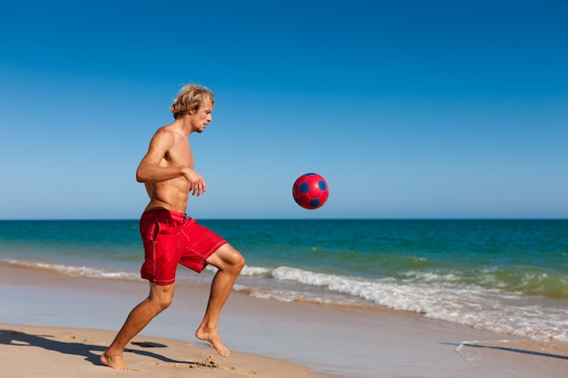 Homme, plage, football jouant