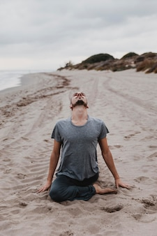 Homme sur la plage pratiquant la relaxation yoga