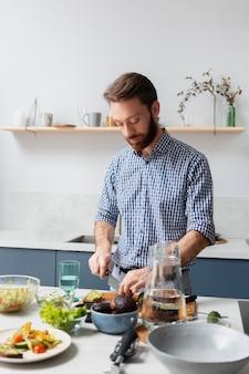 Homme de plan moyen cuisinant seul