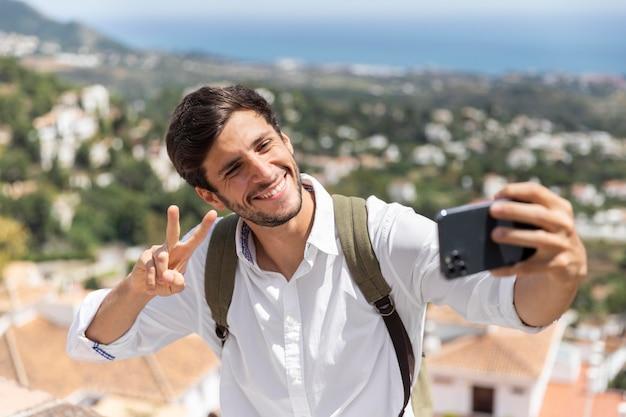Homme de plan moyen prenant des selfies