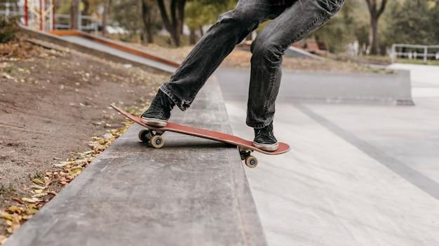 Homme avec planche à roulettes dans le parc de la ville