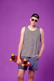 Homme avec planche à roulettes à la main sur fond violet, penny little board