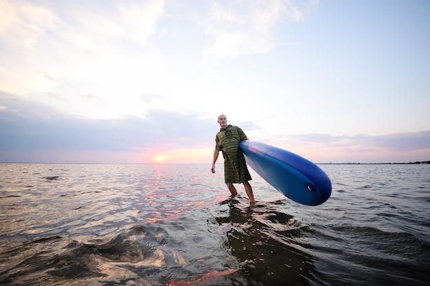 Homme sur une planche de sup contre un beau coucher de soleil et la mer
