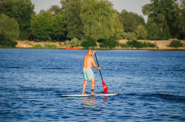 Homme sur une planche de sup dans la rivière
