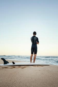 Homme et planche de surf à l'océan