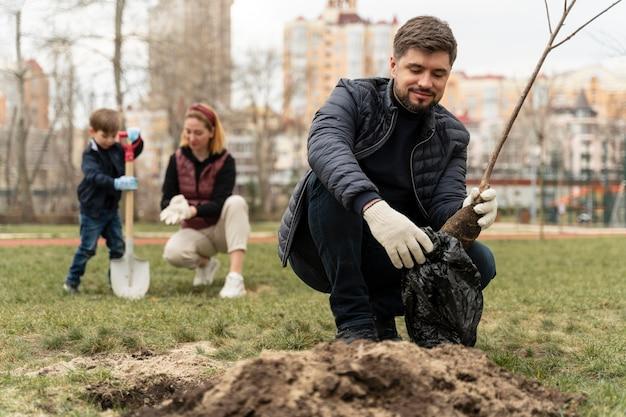 Homme plaquant dans le sol un petit arbre
