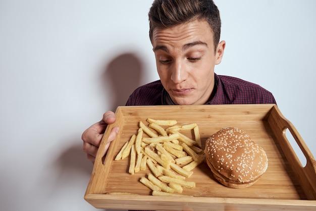 Homme avec un plateau de malbouffe: hamburger et frites, bière