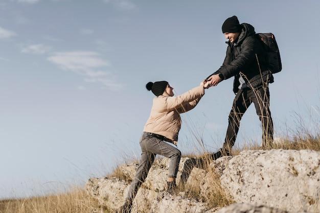Homme plein coup aidant la femme à grimper