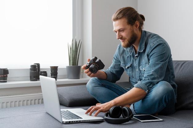 Homme plein coup avec appareil photo et ordinateur portable