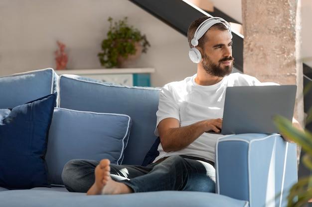 Homme plein coup sur canapé avec ordinateur portable
