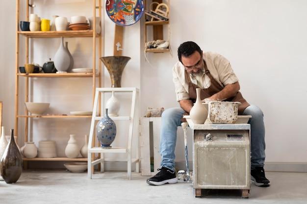 Homme plein coup faisant de la poterie