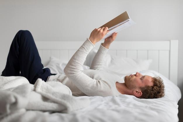 Homme plein coup lisant au lit